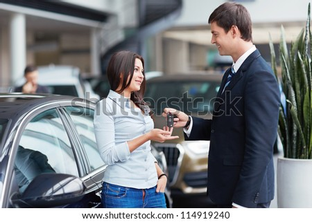 Seller gives keys to car girl in the salon - stock photo