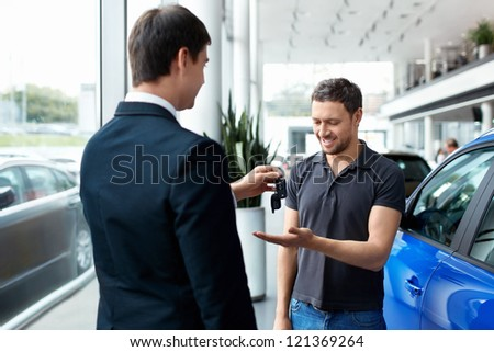 Seller gives the buyer of the car keys - stock photo