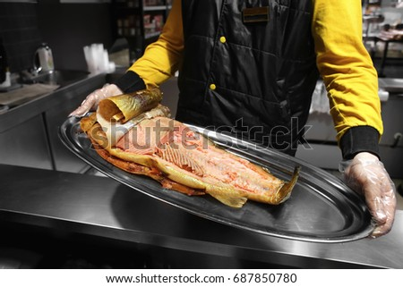 Seller holding tray with smoked fish in supermarket