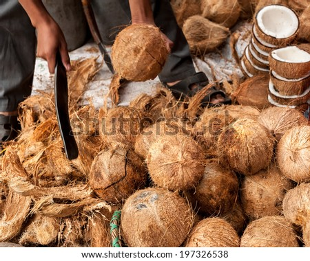 Seller opens tropical coconuts  at traditional food marketplace  - stock photo