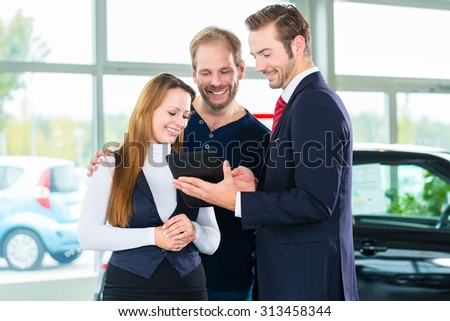 Seller or car salesman and clients or customers in car dealership presenting the interior decoration of new and used cars in the showroom on tablet computer - stock photo