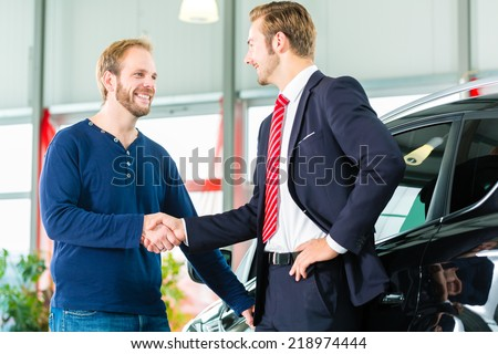 Seller or car salesman and customer in dealership, they shaking hands and seal the purchase of the auto or new car - stock photo