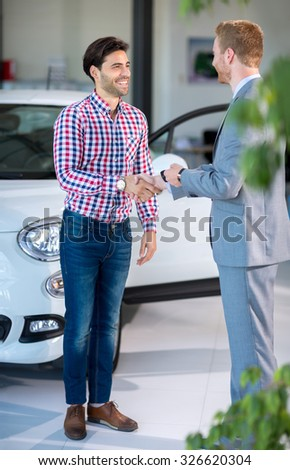 Seller or car salesman and customer in dealership, they shaking hands and seal the purchase of the auto or new car. - stock photo