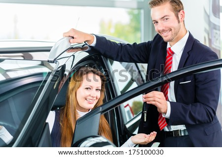 Seller or car salesman and female client or customer in car dealership presenting the interior decoration of new and used cars in the showroom and hands over the car keys - stock photo