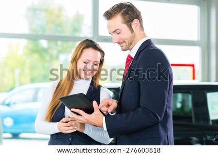Seller or car salesman and female client or customer in car dealership presenting the interior decoration of new and used cars in the showroom on tablet computer - stock photo