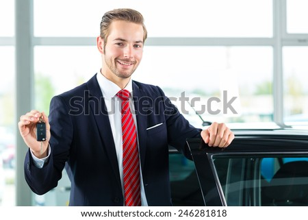 Seller or car salesman in car dealership with key presenting his new and used cars in the showroom - stock photo