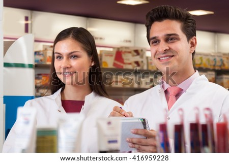 Sellers at the pharmacy. Smiling woman and a man with a notebook in the hands