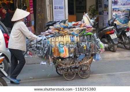 Selling Flip Flops for a living using economical transportation in Hanoi - stock photo