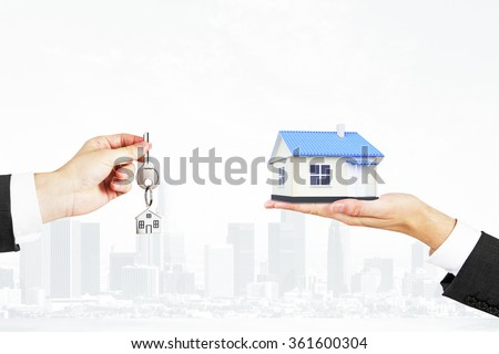 Selling real estate concept with a house and key - stock photo