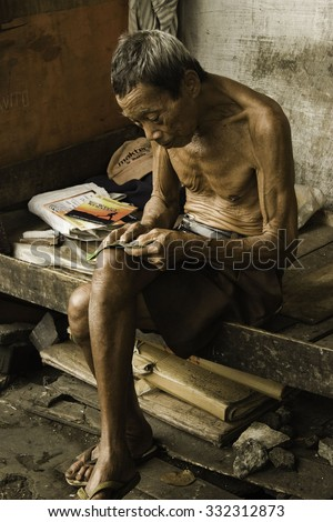 Semarang, Central Java, Indonesia - March 6, 2008 : Old man trying to read a small book without glasses in the old city of Semarang.