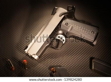 Semi automatic handgun along with ammunition and magazines - stock photo