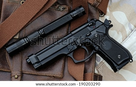 Semi-automatic handgun and tactical flashlight lying over a Leather handbag, 9mm pistol - stock photo