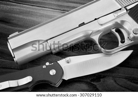 Semi-automatic handgun and tactical knife on wooden background, .45 pistol. (Black & White) - stock photo