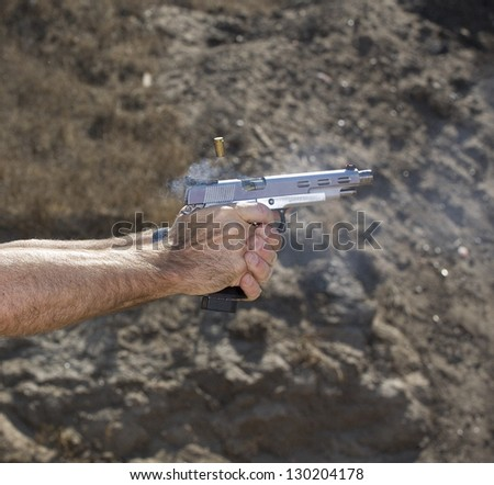 Semi automatic handgun loading another round while brass flies - stock photo
