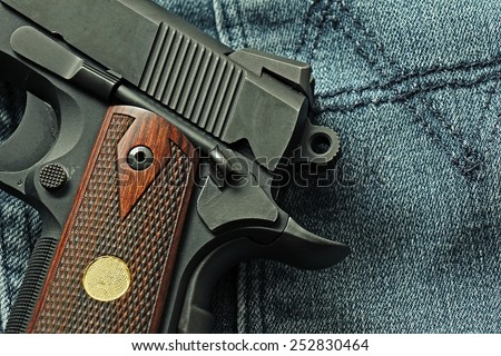 Semi-automatic handgun lying over a blue jeans, .45 pistol, Close-up cock and save. - stock photo