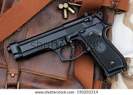 Semi-automatic handgun lying over a Leather handbag, 9mm pistol - stock photo