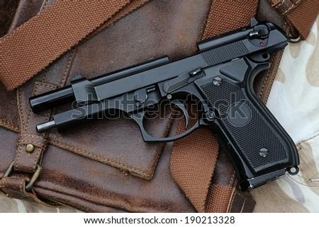 Semi-automatic handgun lying over a Leather handbag, 9mm pistol. - stock photo
