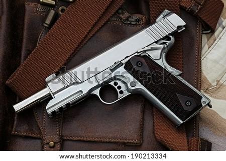 Semi-automatic handgun lying over a Leather handbag, .45 pistol. - stock photo