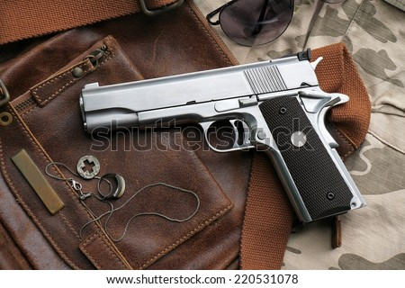 Semi-automatic handgun lying over a Leather handbag, .45 pistol. - stock photo