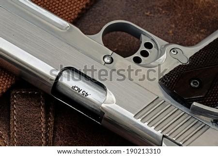 Semi-automatic handgun lying over a Leather handbag, .45 pistol, Close-up. - stock photo