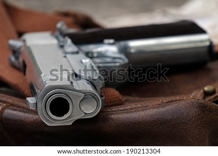 Semi-automatic handgun lying over a Leather handbag, .45 pistol, Close-up Barrel.