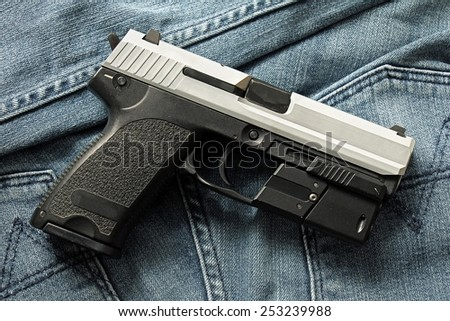 Semi-automatic handgun on blue jeans background, 9mm pistol.