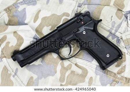 Semi-automatic handgun on camouflage background, Gun on Military texture, 9mm pistol, Modern U.S. Army handgun M9. (Grunge Effect Process)  - stock photo