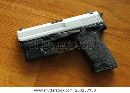 Semi-automatic handgun on wooden background, 9mm pistol. - stock photo