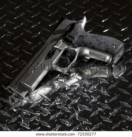 Semi automatic handgun that is on a wet piece of steel - stock photo