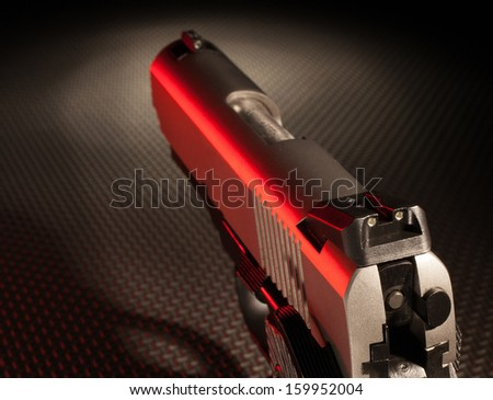 Semi automatic handgun with red highlights seen from the back sights - stock photo