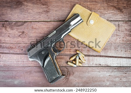 Semi-automatic 9mm gun and leather bag isolated on wooden background. - stock photo