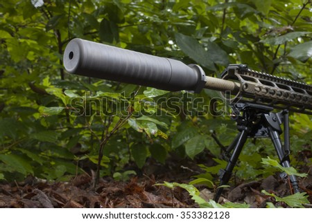 Semi automatic rifle in the brush with a silencer on the barrel - stock photo