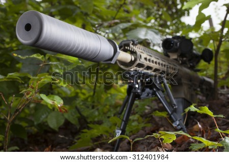 Semi automatic rifle with a suppressor in the trees - stock photo