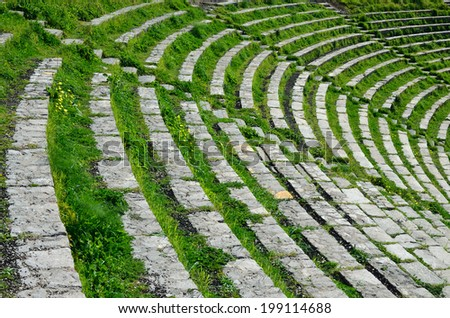 Semi-circular rows of the stone seats are overgrown with green grass in the ancient Greek theatre remaining at Taormina.  - stock photo