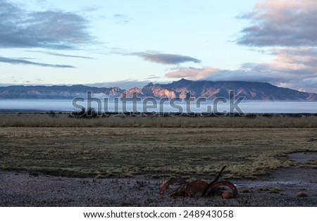 Semi-desert landscape with ground fog at sunlit mountains in winter morning/Pink Sunlight on Mountains with Baseline Ground Fog in Weather Landscape/Pink sunshine on mountains with low fog in winter - stock photo