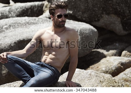 Semi dressed man in jeans on rocks - stock photo