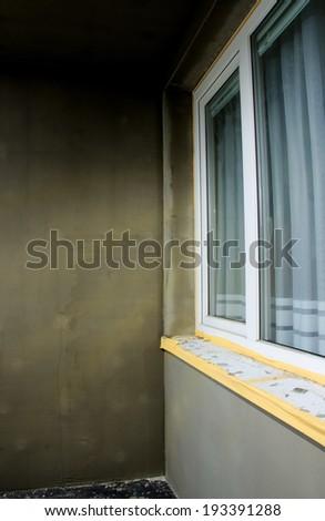 Semi-finished repairing of balcony, gray plaster and dirty white window. - stock photo