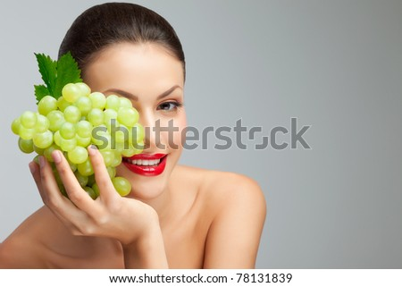 Semi-fruity girl. A sexy young lady hiding her half of face with a bunch of grape. - stock photo