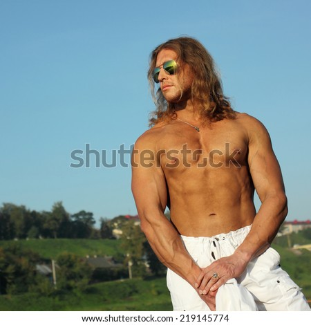 semi nude sexy caucasian fit man in sunglasses posing on the beach in the city - stock photo