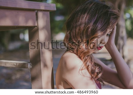 Semi profile portrait of beautiful girl with red hair beside wood tablet