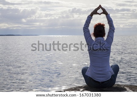 Semi silhouette back light photo-Middle aged  woman in casual clothing  at the seaside meditating and performing Yoga against dramatic cloudy sky - stock photo