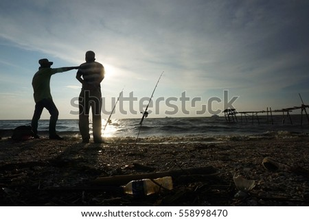 Semi Silhouette of west coast beach in Malaysia 1 hour before sunset on 15th January 2017. Shown in the photo are two fishermen chit chatting while waiting for their fishing rod  in action