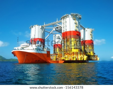 semi submersible heavy lift cargo ship transporting an oil rig - stock photo