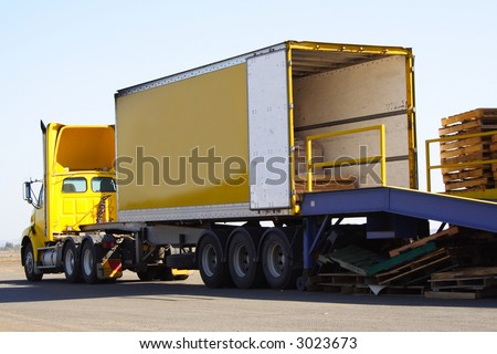 Semi truck backed onto loading ramp - stock photo