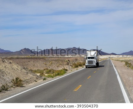 SEMI TRUCK DRIVING ON HIGHWAY, USA  - MARCH 1, 2016: Semi truck going fast on the desert mountain highway  - stock photo