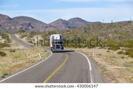 SEMI TRUCK DRIVING ON HIGHWAY, USA - MARCH 16, 2016: Semi truck going fast on the desert mountain highway