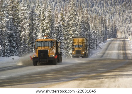 semi truck follows a snowplow