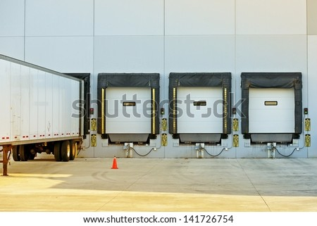 Semi Truck Trailer Warehouse Loading / Unloading. Large Modern American Warehouse Building. Shipping and Cargo Photo Collection. - stock photo