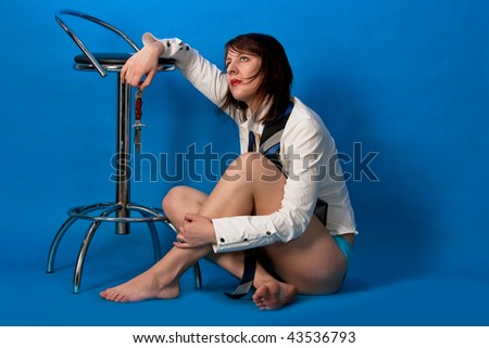 seminude young caucasian girl sitting with calm face holding knife near high chair isolated on blue background - stock photo