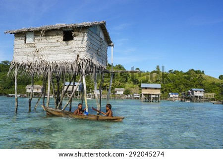 SEMPORNA ISLAND, SABAH, MALAYSIA - JUNE 6 : Unidentified Sea Bajau's children rowing a boat in front of a hut on June 6th, 2014 in Semporna Island, Sabah Malaysia  - stock photo